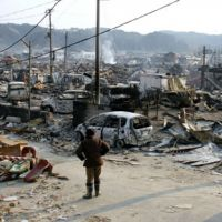 Trying to cope: Residents survey the destruction in the town of Yamada, Iwate Prefecture, on Monday. | KYODO PHOTO