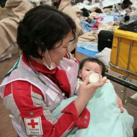 Lucky one: A baby who survived last Friday's mega-quake is fed milk by a member of the Japanese Red Cross National Disaster Response Team at Ishinomaki Red Cross Hospital in Ishinomaki on Saturday. The photo was provided by the Japanese Red Cross Society. | AP PHOTO