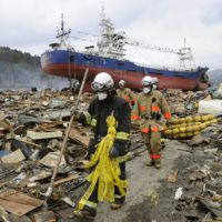 Where to begin: Firefighters search tsunami-devastated areas of Kesennuma, Miyagi Prefecture, on Tuesday as a big ship lies high and dry among the debris. | KYODO PHOTO