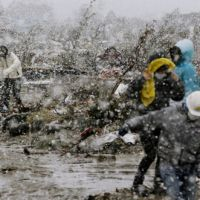 Quake survivors brave a snowfall to dig for belongings where their homes once stood in Sendai. | KYODO PHOTO