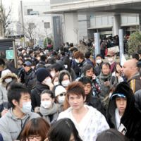 Safer at home: Foreign nationals line up at the Tokyo Regional Immigration Bureau in Minato Ward on Wednesday. Most sought a re-entry permit so they can go home and return to Japan when the situation is safe. | SATOKO KAWASAKI PHOTO