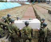 Cremation deferred: Self-Defense Forces personnel prepare to bury a tsunami victim Tuesday at a cemetery in Higashimatsushima, Miyagi Prefecture. | KYODO PHOTO