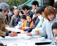 Hot meals: Volunteers (left) distribute food to Fukushima Prefecture evacuees at Tokyo Budokan in Adachi Ward. | SATOKO KAWASAKI PHOTO