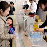 On the safe side: A mother with her baby receives bottled water Thursday at the Shibaura branch of the Minato Ward office in Tokyo amid public concern that tap water is contaminated with radioactive iodine. | YOSHIAKI MIURA PHOTO