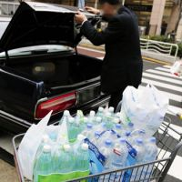 Liquid load: A man loads his car with water bottles Wednesday outside a Tokyo supermarket, after the metropolitan government issued an advisory for residents in its 23 wards and five cities not to give infants younger than 1 year old tap water due to a high level of radioactive iodine. | KYODO PHOTO
