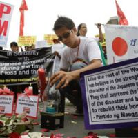 Sending sympathies: A man arranges a candle during a solidarity rally in front of the Japanese Embassy in Pasay City, south of Manila, on Thursday. | AP PHOTO