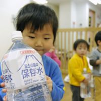 Just a precaution: A child holds a bottle of water at a nursery in Koto Ward, Tokyo, on Thursday. | KYODO PHOTO