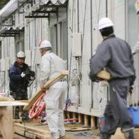 New accommodations: Workers construct temporary housing in Rikuzentakata, Iwate Prefecture, on Saturday, for survivors of the March 11 earthquake and tsunami. | KYODO PHOTO