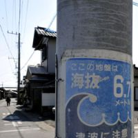 A tsunami warning sign, looking decades-old, adorns a utility pole.