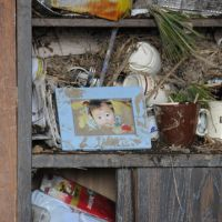 Topsy-turvy: A photo of a child sits on a cabinet shelf in a house in Wakabayashi Ward, Sendai, on Tuesday. | SATOKO KAWASAKI PHOTO