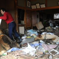Broken home: A man cleans up at his quake- and tsunami-hit home in Sendai's Wakabayashi Ward Tuesday. | SATOKO KAWASAKI PHOTO