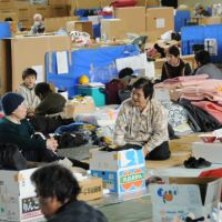 Under the same roof: Evacuees sit in the city-run Wakabayashi Gymnasium in Sendai on Tuesday. | SATOKO KAWASAKI PHOTO