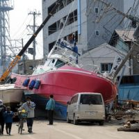 People pass boats Wednesday left by the March 11 tsunami in Ishinomaki, Miyagi Prefecture. | SATOKO KAWASAKI PHOTO