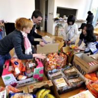 One community: Abi (left) and Roger Lowther (second from left), missionaries with Grace City Church Tokyo, gather with other volunteers at a community room in Tokyo's Tsukishima neighborhood to pack boxes of donated goods to send up north to the disaster areas. | YOSHIAKI MIURA PHOTO