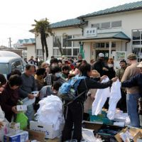 Just your size: Volunteers distribute relief supplies at JR Watanoha Station in Ishinomaki, Miyagi Prefecture, on Thursday. | SATOKO KAWASAKI PHOTO