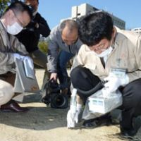 Measured response: Prefectural workers monitor radiation levels at an elementary school in the city of Fukushima on Tuesday. The checks at schools across the prefecture were prompted by inquiries from concerned parents. | KYODO PHOTO