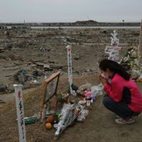 Moment of silence: A survivor prays in an area destroyed by the March 11 tsunami in Natori, Miyagi Prefecture, on Monday. | AP PHOTO