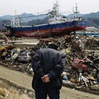 Hasn't gone away: An elderly man observes an area devastated by the giant quake and tsunami in Kesennuma, Miyagi Prefecture, on Monday, exactly a month after the disaster. | AP PHOTO