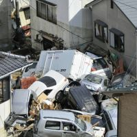 No way out: Vehicles swept away by the March 11 tsunami are piled up in Kesennuma, Miyagi Prefecture, on March 12. Survivors say traffic jams following the quake added to the tsunami death toll. | KYODO PHOTO