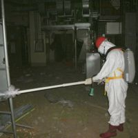 Danger zone: A worker measures radiation levels inside the building housing the No. 1 reactor of the Fukushima No. 1 nuclear power plant on Thursday. | KYODO