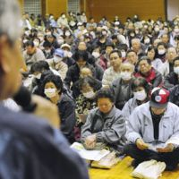 Stony silence: Residents who were forced to evacuate from their homes in Iitate, Fukushima Prefecture, listen to Norio Tsuzumi, executive vice president of Tokyo Electric Power Co., speak about the crippled Fukushima No. 1 nuclear plant April 30. | KYODO PHOTO