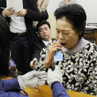 DNA detective: Chiyoko Sasaki swabs her mouth to take a DNA sample Friday at the Azuma Gymnasium in the city of Fukushima. The sample will be used in a bid to find a family member missing since the March 11 quake and tsunami. | KYODO PHOTO