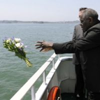 Special significance: Cardinal Robert Sarah throws flowers into the ocean during prayers for victims of the March 11 earthquake and tsunami as he rides on a sightseeing boat in Matsushima Bay, Miyagi Prefecture, on Monday. | KYODO PHOTO