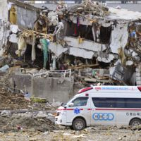 Life saver: An ambulance passes rubble in the tsunami-hit town of Onagawa, Miyagi Prefecture, on March 18. | KYODO
