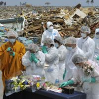 Covered in grief: Dressed in protective clothing, residents of Namie, Fukushima Prefecture, burn incense and pray Thursday for those who died in the March 11 monster earthquake and tsunami that crippled the Fukushima No. 1 nuclear plant and forced them to evacuate. | KYODO PHOTO