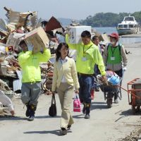 Providing relief: Volunteer workers move aid supplies last week in tsunami-hit Shiogama, Miyagi Prefecture. | KYODO
