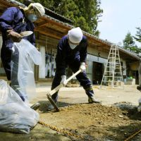 Cleanup: Members of a nonprofit organization scrape up soil from outside a private home in Iitate, Fukushima Prefecture, on May 20 in a bid to reduce emissions of radioactive substances in the area. | KYODO