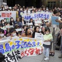 Seeking guidance: Fukushima Prefecture parents and their children protest the education ministry's radiation safety standards at schools outside the ministry in Tokyo on May 23. | KYODO PHOTO