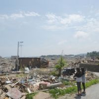 Live goes on: Marivel Gunji (left) and Rachel Takahashi look at a tsunami-ravaged neighborhood in Kesennuma, Miyagi Prefecture, in late May.