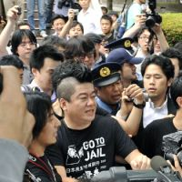Sporting a mohawk haircut and T-shirt saying 'Go to jail,' Takafumi Horie, the founder and former president of Internet firm Livedoor Co., arrives Monday at the Tokyo High Public Prosecutor's Office as his imprisonment over accounting fraud begins. | KYODO PHOTO