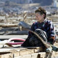 Face of despair: Fujiko Sato, 82, sits on the flattened remains of her home in Rikuzentakata, Iwate Prefecture, on April 5. | ROB GILHOOLY