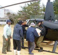 Glenn hands out supplies to evacuees in Ajishima, Miyagi Prefecture, on April 4. | HELICOPTER CONFERENCE OF JAPAN