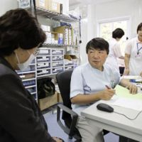 Ready care: A female patient sees a doctor Monday at tsunami-hit Otsuchi Hospital in Otsuchi, Iwate Prefecture, after it resumed services at a prefabricated clinic. | KYODO PHOTO