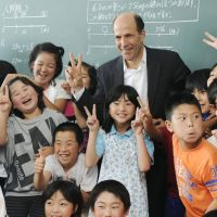 Tomodachi: U.S. Ambassador John Roos poses with students of Komezaki Elementary School in Rikuzentakata, Iwate Prefecture, on Tuesday morning. | KYODO