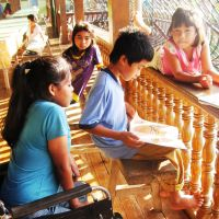 It is written: Students at the Mindanao Children's Library Foundation set up by Tomo Matsui in Kidapawan, the Philippines, read a book June 26. | KYODO