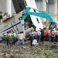 End of the line: Workers watch as cars of a high-speed train are demolished Sunday after a deadly rear-ender crash Saturday in Wenzhou, Zhejiang Province. | KYODO PHOTO