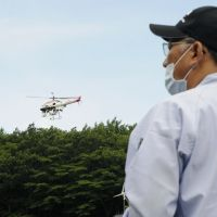 Eye in the sky: An official operates an unmanned helicopter in Kawauchi, Fukushima Prefecture, on Wednesday as part of efforts to gauge the radiation levels of parks, schools, hospitals and other locations in areas designated as hot spots. | KYODO