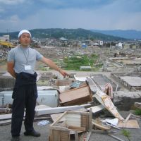 Building on a dream: Masaharu Takagi points at the planned fireworks launchpad on the debris-filled beach of Hisanohama in Fukushima Prefecture on July 10. Stages for performers will also be built there for the event scheduled for Aug. 27. | MINORU MATSUTANI