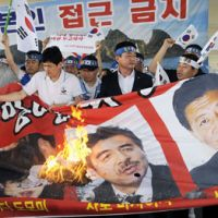 Conservative backlash: South Korean protesters burn a banner with pictures of three Liberal Democratic Party lawmakers, including Yoshitaka Shindo (right), at Gimpo International Airport on Monday. | KYODO PHOTO