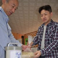 Skeptical: Takenori Chiba (right), of Fukushima Prefecture, hands shredded potatoes to staff at the Citizens' Radioactivity Measuring Station in the city of Fukushima on Monday. | KYODO