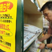 Grain strain: An employee checks dwindling rice stocks Thursday at a supermarket in Chuo Ward, Tokyo, next to a sign that says the last shipment of 2010 Koshihikari arrived Monday from Niigata Prefecture and this year's crop will reach shelves around late September. | KYODO