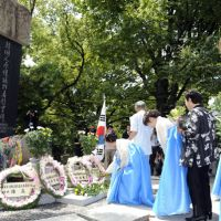 Lest we forget: Korean residents pray Friday in front of the monument commemorating Korean victims of the Aug. 6, 1945, atomic bombing of Hiroshima, at Peace Memorial Park. | KYODO