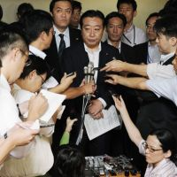 On the job: Finance Minister Yoshihiko Noda is surrounded by reporters at the ministry Monday after finishing a phone conference with his counterparts of the G-7 developed countries. | KYODO