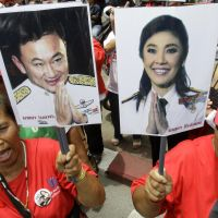 Informal Thais: Supporters of the Pheu Thai Party, holding portraits of former Thai Prime Minister Thaksin Shinawatra and his sister, Yingluck Shinawatra, cheer outside Parliament in Bangkok on Aug. 5. | AP