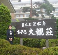 Still standing: Yuko Isoda, general manager of the Taikanso hotel in Matsushima, Miyagi Prefecture, poses at the inn's entrance on Aug. 4. Below: A March 31 photo of Matsushima Bay shows how the town escaped large-scale destruction. | ALEX MARTIN, SATOKO KAWASAKI