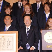 Spoils of victory: Surrounded by members of the national women's soccer team, coach Norio Sasaki (front left) and captain Homare Sawa show off the People's Honor Award certificate and plaque at an award ceremony with Prime Minister Naoto Kan in Tokyo on Thursday. | AP PHOTO